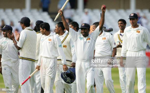 Sri Lanka's Muttiah Muralitharan celebrates with a souvenir stump and the match ball as he leaves the field having taken eight wickets in the second...