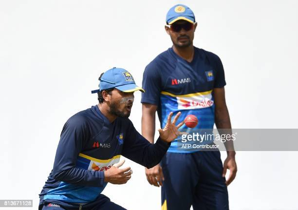 Sri Lanka's new Test cricket captain Dinesh Chandimal catches the ball as teammate Danushka Gunathilaka looks on during a practice session at the R...