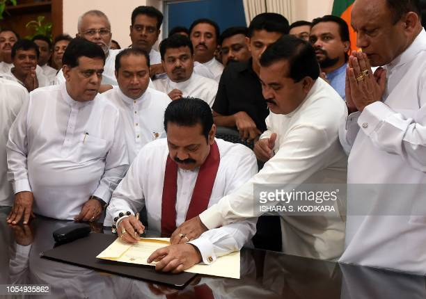 Sri Lanka's newly appointed Prime Minister Mahinda Rajapaksa signs a document during a ceremony to assume duties at the prime minister's office in...