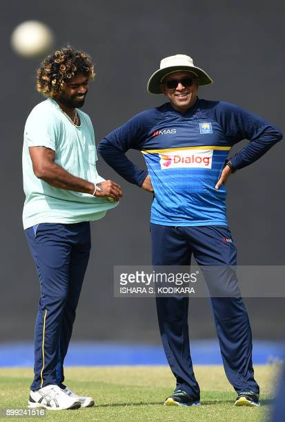 Sri Lanka's newlyappointed head cricket coach Chandika Hathurusingha speaks with player Lasith Malinga during a practice session at the R Premadasa...