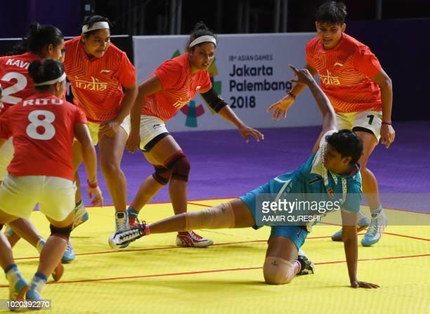 Sri Lanka's Nimashi Kokila E Edirisinghage tries to a score as India's players defend during the women's team Group A kabaddi match between India and...