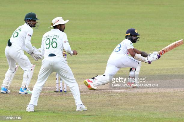 Sri Lanka's Niroshan Dickwella plays a shot as Bangladesh's wicketkeeper Liton Das and Saif Hassan watch during the fourth day of the second and...
