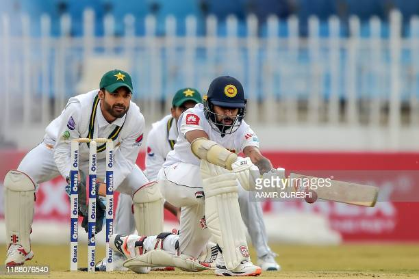 Sri Lanka's Niroshan Dickwella plays a shot as Pakistan's wicketkeeper Mohammad Rizwan looks on during the second day of the first Test cricket match...