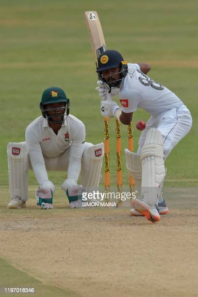 Sri Lanka's Oshada Fernando plays a shot as Zimbabwe's Regis Chakabva looks on during the second day of the second Test cricket match between...
