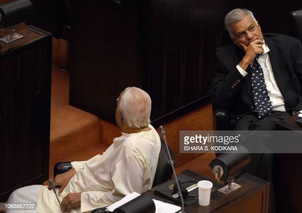 Sri Lanka's ousted prime minister Ranil Wickremesinghe and opposition leader R Sampanthan look on at the parliament chamber as members of President...