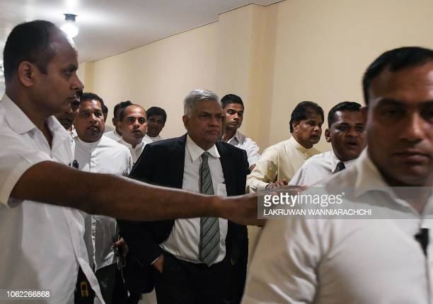 Sri Lanka's ousted prime minister Ranil Wickremesinghe leaves parliament escorted by security personnel and aides in Colombo on November 16, 2018. -...