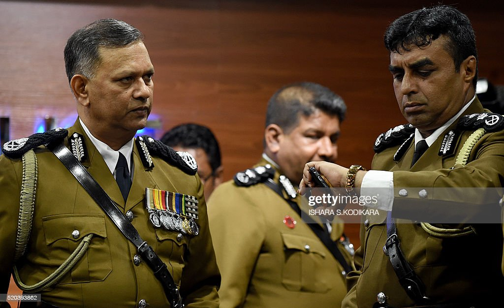 Sri Lankas outgoing police chief N. K. Illangakoon(L)looks on as another officer Pujith Jayasundara checks his watch at police headquarters in Colombo on April 11, 2016, ahead of starting his final meeting with officers and men. A new appointment is due to be made in over a week in line with new constitutional provisions aimed at de-politicising the police department. / AFP / ISHARA