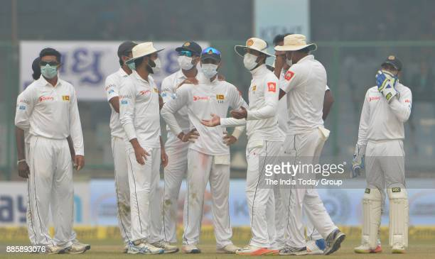 Sri Lanka's players gathers wearing antipollution masks during the second day of their third test cricket match in New Delhi
