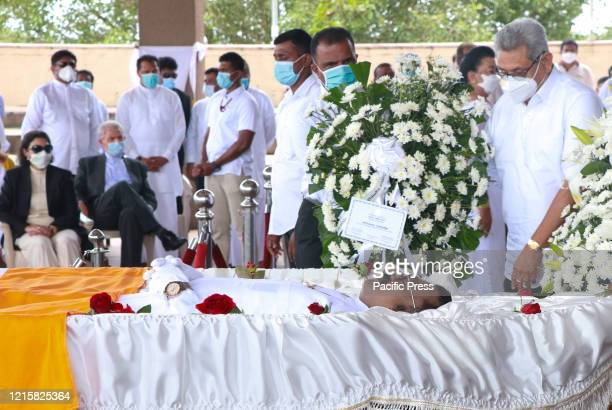 Sri Lanka's President Gotabhaya Rajapaksa presents a wreath to pay his respects during the funeral of Ceylon Workers' Congress trade union leader...