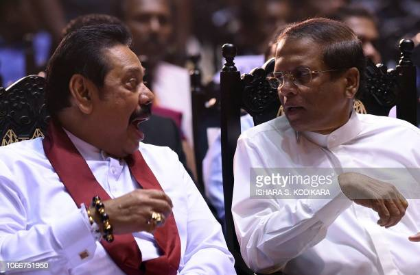 Sri Lankas President Maithripala Sirisena speaks with former president and currently appointed prime minister Mahinda Rajapaksa at a ceremony...
