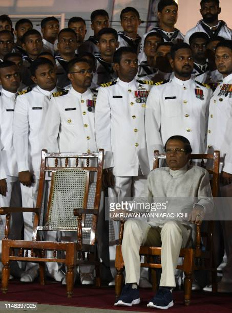 Sri Lanka's President Maithripala Sirisena waits next to Navy officers for a group photo during a ceremony commissioning P 626 ship US gifted to the...