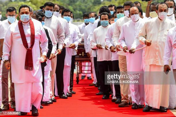 Sri Lanka's Prime Minister Mahinda Rajapaksa and former speaker of the Parliament Karu Jayasuriya attend a laying in state ceremony for late tea...