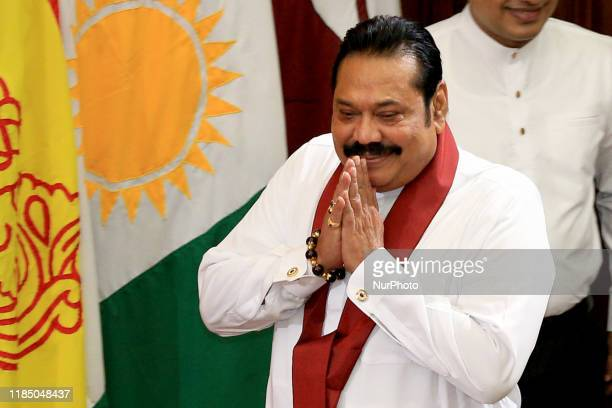 Sri Lanka's prime minister Mahinda Rajapaksa greets as he arrives at a ministerial swearing-in ceremony at the Presidential Secretariat in Colombo,...