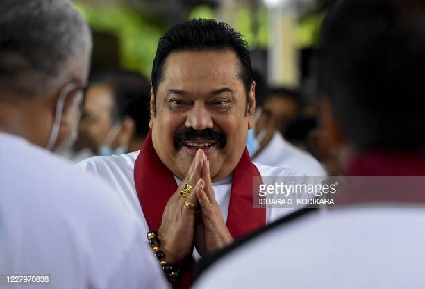 Sri Lanka's Prime Minister Mahinda Rajapaksa greets as he arrives at his swearing-in ceremony at the sacred Kelaniya Raja Maha Buddhist temple,...