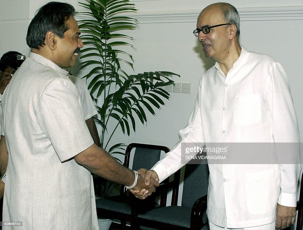 Sri Lanka's Prime Minister Mahinda Rajapakse (L) shakes hands with Indian envoy, Nirupam Sen at his official residence in Colombo, 20 May 2004. Sri Lanka is seeking support from other Test cricket playing nations in the region to defend bowler Muttiah Muralitharan who has set a world record for the highest number of Test wickets and may have his unique 'Doosra' deivery banned by the sport's governing body. AFP PHOTO/Sena VIDANAGAMA