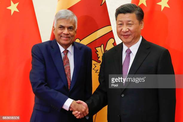 Sri Lanka's Prime Minister Ranil Wickremesinghe shakes hands with Chinese President Xi Jinping as they meet at the Great Hall of the People on May 16...