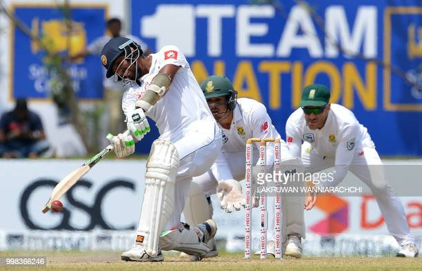 Sri Lanka's Suranga Lakmal plays a shot in front of South Africa's wicketkeeper Quinton de Kock and Faf du PLessis during the third day of the...