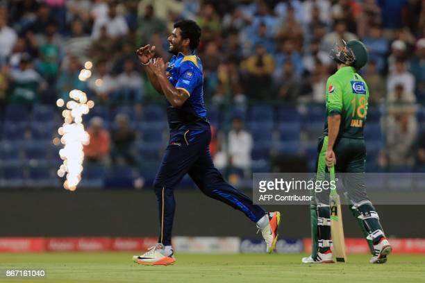 Sri Lanka's Thisara Perera celebrates taking the wicket of Pakistan's Ahmed Shehzad next to Pakistan's Shoaib Malik during the second Twenty20 series...