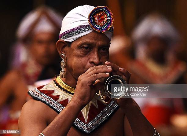 Sri Lanka's traditional dancer plays traditional music and performs in front of the historic Buddhist Temple of the Tooth, as he takes part in a...
