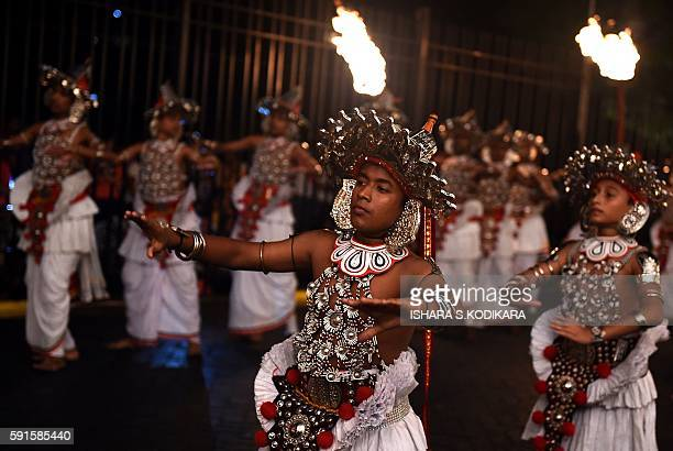 Sri Lanka's traditional dancers perform in front of the historic Buddhist Temple of the Tooth, as they take part in a procession during the Esala...