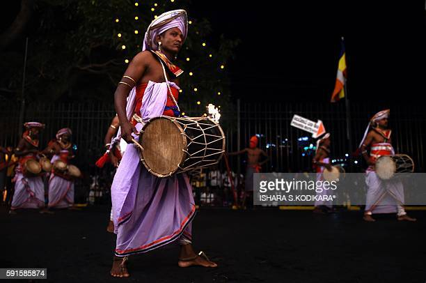 Sri Lanka's traditional dancers play traditional music and perform in front of the historic Buddhist Temple of the Tooth, as they take part in a...