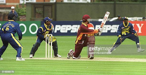 Sri Lanka's wicket keeper Romesh Kaluwitharana and fielder Hashan Tillekeratne keep their eyes on the ball as Matthew Hayden of Northampton hits out...