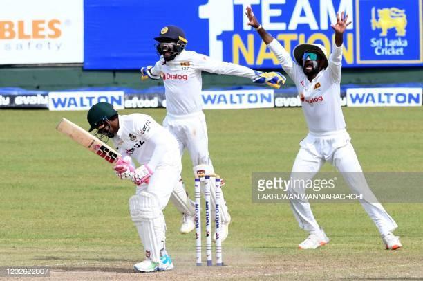 Sri Lanka's wicketkeeper Niroshan Dickwella and teammate Lahiru Thirimanne celebrate after the dismissal of Bangladesh's Mushfiqur Rahim during the...