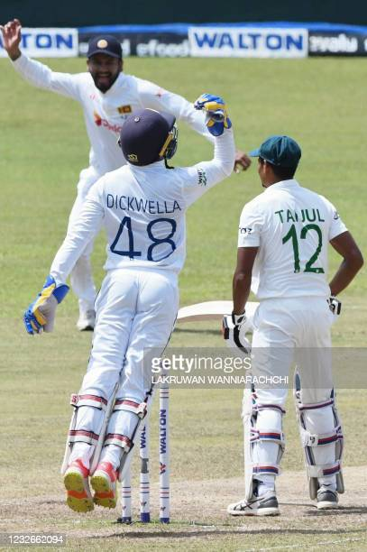 Sri Lanka's wicketkeeper Niroshan Dickwella celebrates after a catch to dismiss Taijul Islam during the final day of the second and final Test...