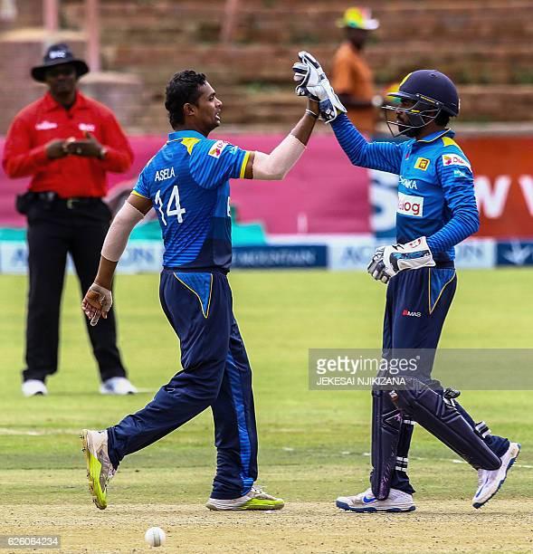 Sri Lanka's wicketkeeper Niroshan Dickwella celebrates the wicket of Zimbabwe's batsman Tendai Chisoro with Sri Lanka's bowler Asela Gunaratne during...