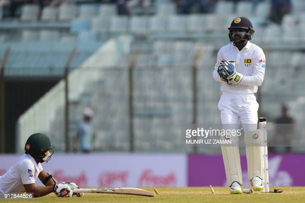 Sri Lanka's wicketkeeper Niroshan Dickwella successfully breaks the stumps as Bangladeshi batsman Mehidy Hasan looks on during the second day of the...