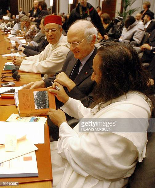 Sri Sri Ravi Shankar talks to an unidentified person during the first World Congress of Imams and Rabbis for Peace attended by various religious...