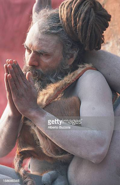 Sri Tikambar Shiva Raj Gii Baba a holy man of the Naga Baba congregation shows his yoga skills on the Ghats of the Ganges River