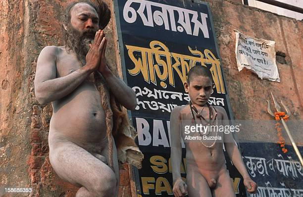 Sri Tikambar Shiva Raj Giri Baba preparing himself for yoga exercises on the bank of the Ganges River accompanied by one of his students Sri Tikambar...
