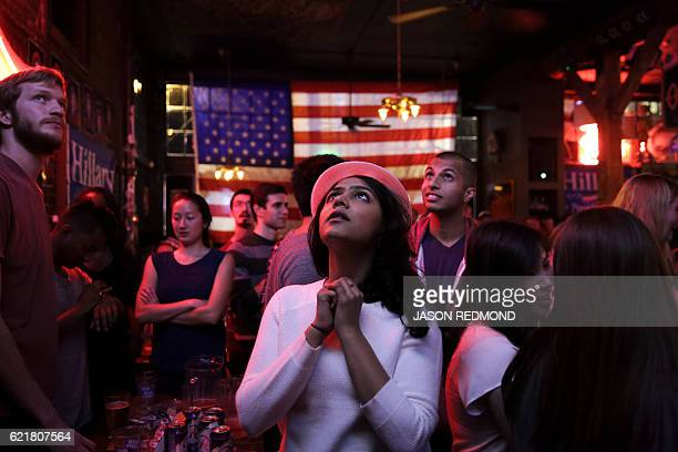 TOPSHOT Sri Vasamsetti of Seattle and a supporter of Democratic presidential candidate Hillary Clinton watches televised coverage of the US...