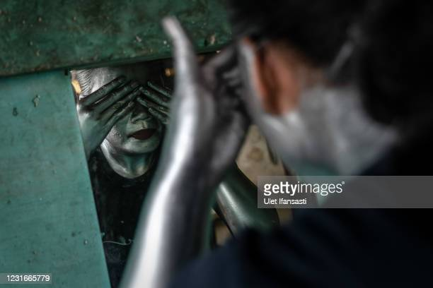 Sri Winarti , is three months pregnant, wearing silver paint as prepare for beg on the street on March 10, 2021 in Depok, Indonesia. 'Silver Men',...