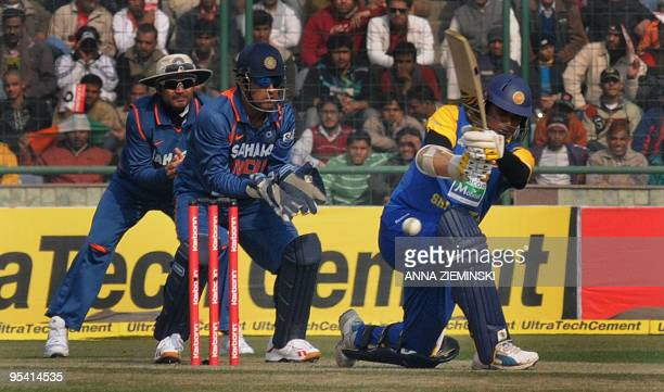 Sri8 Lankan cricketer Thilina Kandamby is watched by Indian wicketkeeper Mahendra Singh Dhoni and fielder Virender Sehwag as he hits a boundary...