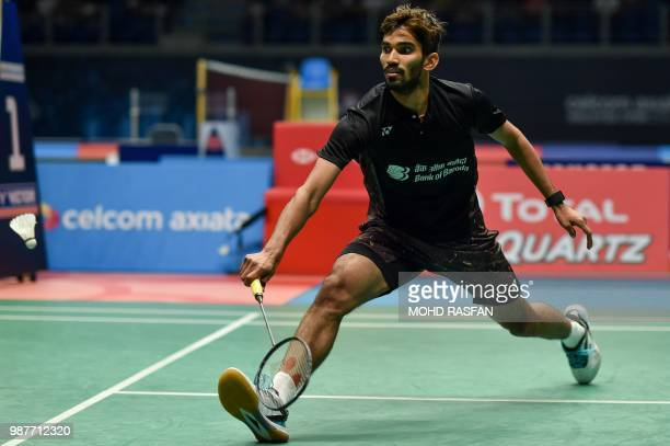 Srikanth Kidambi of India hits a return against Kento Momota of Japan in their men's singles semifinal match at the Malaysia Open Badminton...