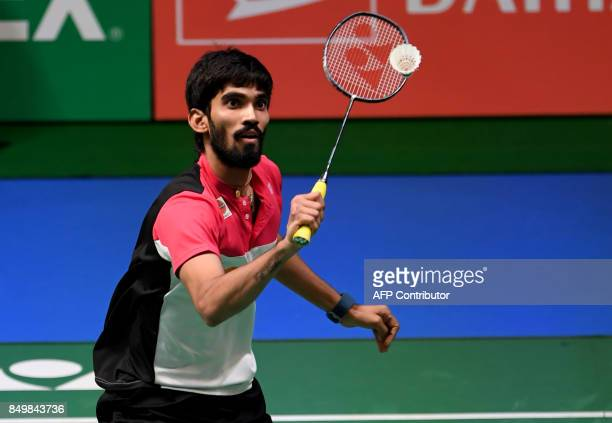 Srikanth Kidambi of India hits a return against Tian Houwei of China during their men's singles first round match at the Japan Open Badminton...