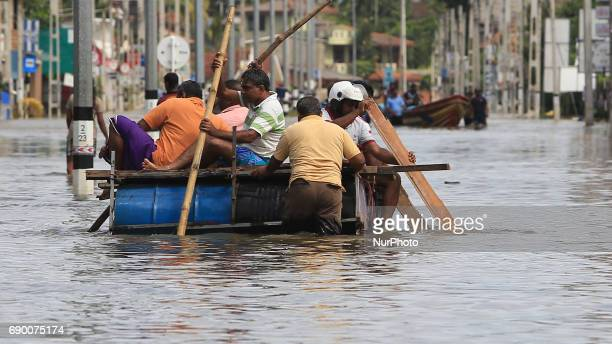 Srilankan men row a makeshift raft on a flooded road in Godagama Matara Sri Lanka Tuesday 30 May 2017