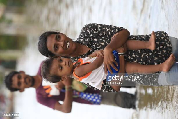A Srilankan woman walks through a flooded road with her baby in Godagama Matara Sri Lanka Tuesday 30 May 2017
