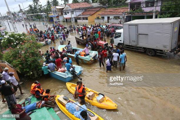 Srilankans wait for relief item near flooded road in Godagama Matara Sri Lanka Tuesday 30 May 2017