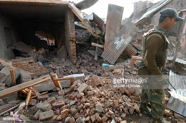An Indian soldier stands in the rubble of flattened houses which were destroyed in a fight between Islamic rebels and Indian security forces at...