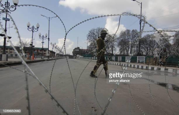 Srinagar Kashmir India Indian policemen stand guard near barbed wire during an undeclared curfew in Srinagar the summer capital of Indian Kashmir 09...