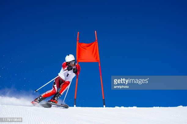 sskier in race suit during super g skiing training close to red poles flag at perfect weather conditions - ski racing stock pictures, royalty-free photos & images