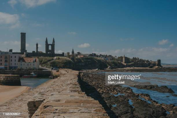 st andrews pier with cathedral and castle visible in the background - st. andrews scotland stock photos and pictures