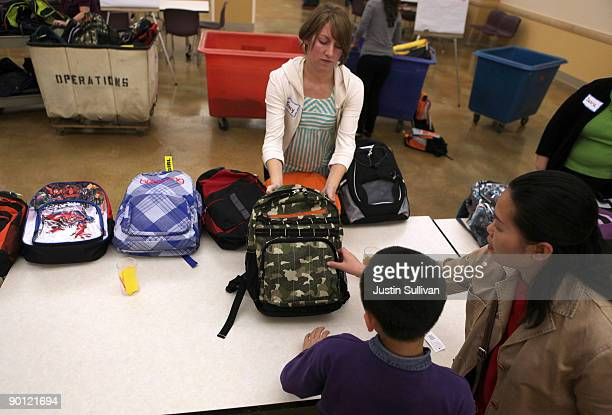 St Anthony Foundation volunteer Tracy Gallagher helps choose a backpack filled with school supplies for a young boy August 27 2009 in San Francisco...
