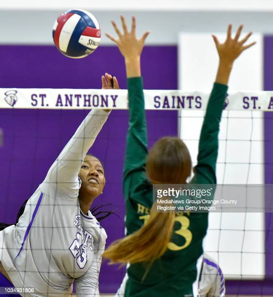 St Anthony's Stacy Tope left hits around Adrianna Hebert's block in Long Beach on Tuesday October 11 2016 St Anthony vs St Monica girls...