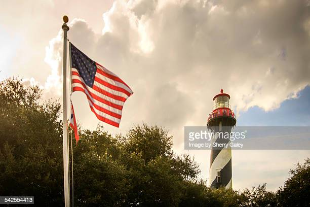 st. augustine lighthouse with u.s. flag - st augustine lighthouse stock photos and pictures
