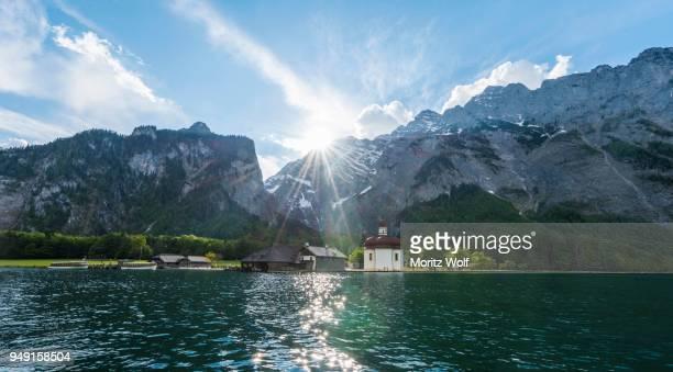 st. bartholomews church, koenigssee, lake, watzmann mountain with sunbeams, berchtesgaden national park, berchtesgadener land, upper bavaria, bavaria, germany - berchtesgaden national park stock photos and pictures