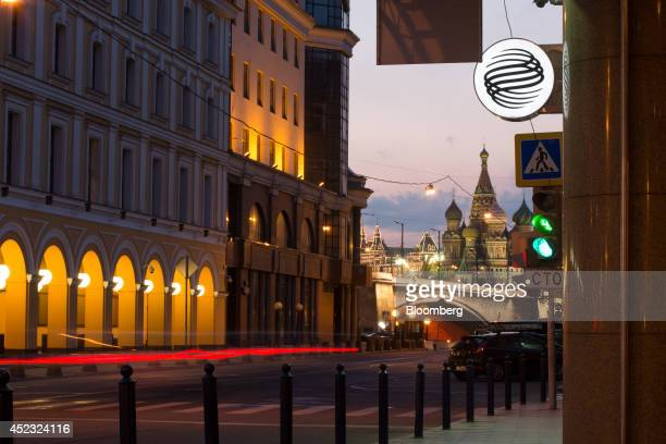 St Basil's Cathedral stands in the distance beyond an illuminated logo outside an OAO Gazprombank bank branch in Moscow Russia on Thursday July 17...